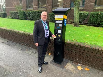 Councillor Burrows standing in front of a new parking machine
